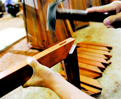 王新华   榫卯结构在中国运用的历史源远流长,是红木家具的一大特色。许多明清时期的红木家具距今已几百年历史了,虽略显陈旧,但家具整体的结构仍然完好如初,其中榫卯结构功不可没。  榫卯,是红木家具中相连接的两构件上采用的一种凹凸处理接合方式凸出来的榫头和凹进去的卯眼扣在一起,两块木头就会紧紧地相握,不再分离。大范之家红木家具总经理刘新文说,红木家具自明末进入技艺之巅峰后,代代相传、绵延至今,如今已成为世界文化遗产的一部分,其灵魂就是榫卯结构。一套红木家具不使用一根铁钉,却能使用几百年甚至上千年,堪