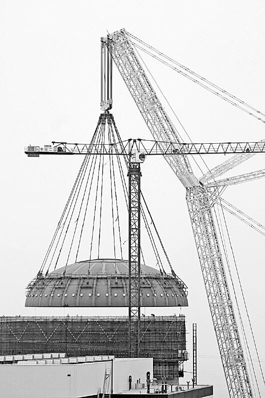 记者 左丰岐 李檬 报道   本报海阳讯 8月4日17时28分,三代核电自主化依托项目海阳2号机组核岛钢制安全壳顶封头(简称CVTH)成功吊装就位。    CVTH为半椭球形,由四圈共64块弧形钢板拼装而成,筒体端内径近40米,内高约11.5米,壁厚41.3毫米,吊装总重量约790吨。吊装工作自14时12分开始,其间克服了吊装重量重、迎风面积大、对接精度高、壁厚薄易变形等技术难点,最终顺利就位于钢制安全壳第四环上,共历时3小时16分钟。   CVTH吊装是安全壳的收官之作,也是AP1000核电建设