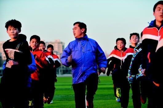 昌乐一中的运动场上,潘来军带领学校足球队的孩子们作热身训练.