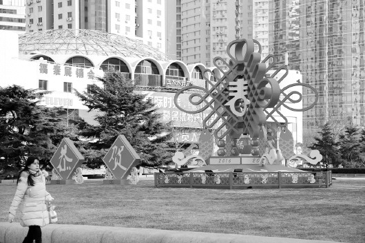 薄克国 报道    2月5日,青岛市民走过五四广场上搭建的中国结雕塑