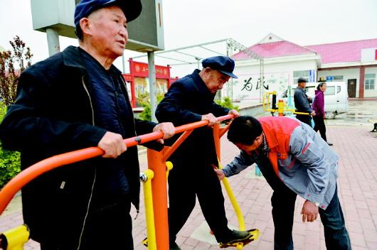 陪护老人们出来活动的崔士山正在教他们如何使用健身器材.