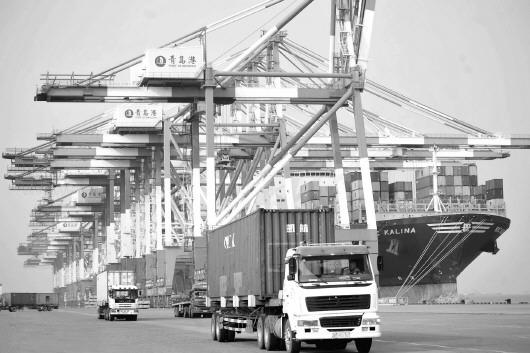 cfp供图    在青岛港码头,货车给集装箱班轮运送集装箱.