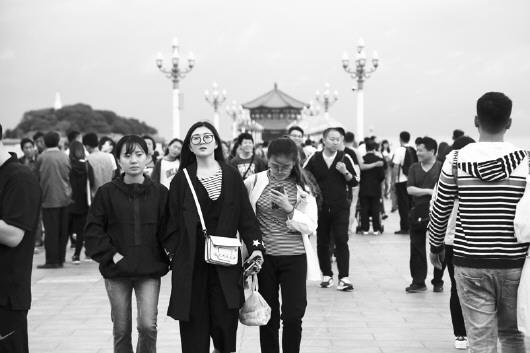 但是青岛栈桥景区还是迎来大批游客,游客在栈桥饱览秋日大海风光.