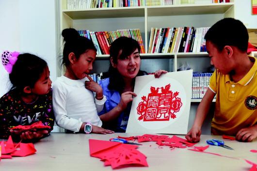 区儿童义务教授剪纸手工课的崔延雪,正在给孩子们讲解自己创作的
